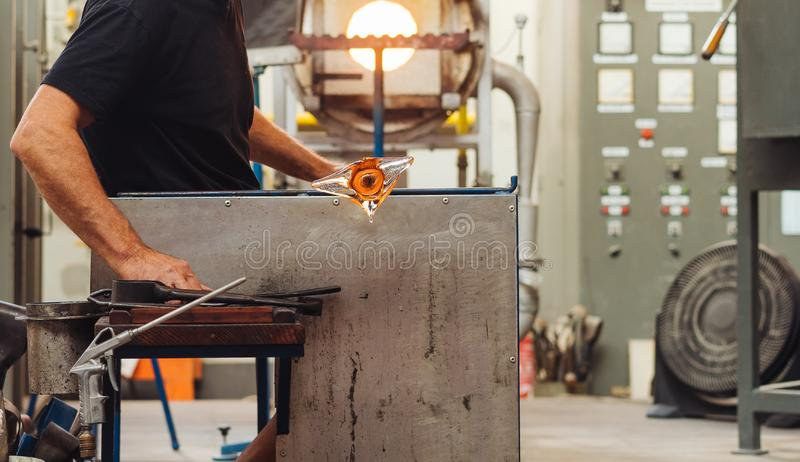 A Glass Blower Shaping Molten Glass into a Piece of Art. Makes a flower stock images