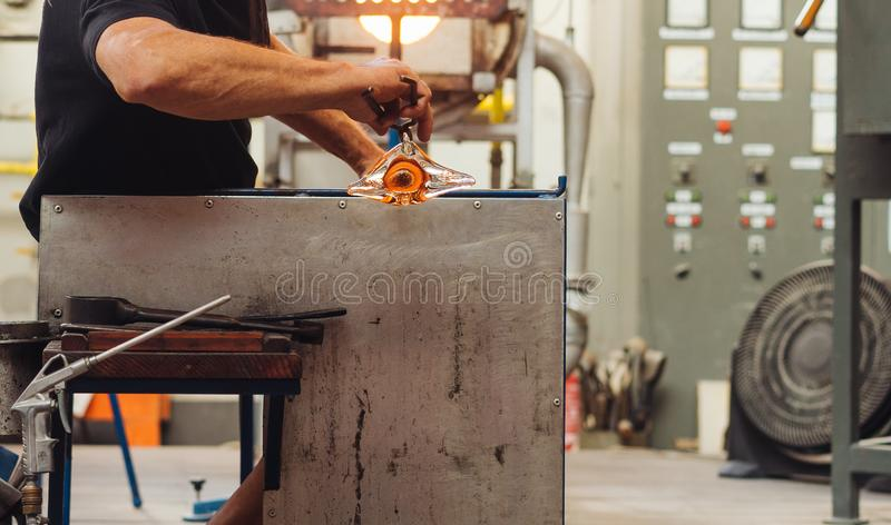 A Glass Blower Shaping Molten Glass into a Piece of Art. Makes a flower royalty free stock images