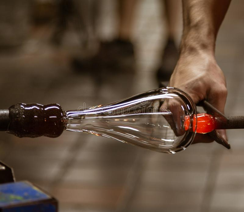 A glass blowing artist forms a blob of glass into a vessel using. Hot forming tool in Vermont stock photo