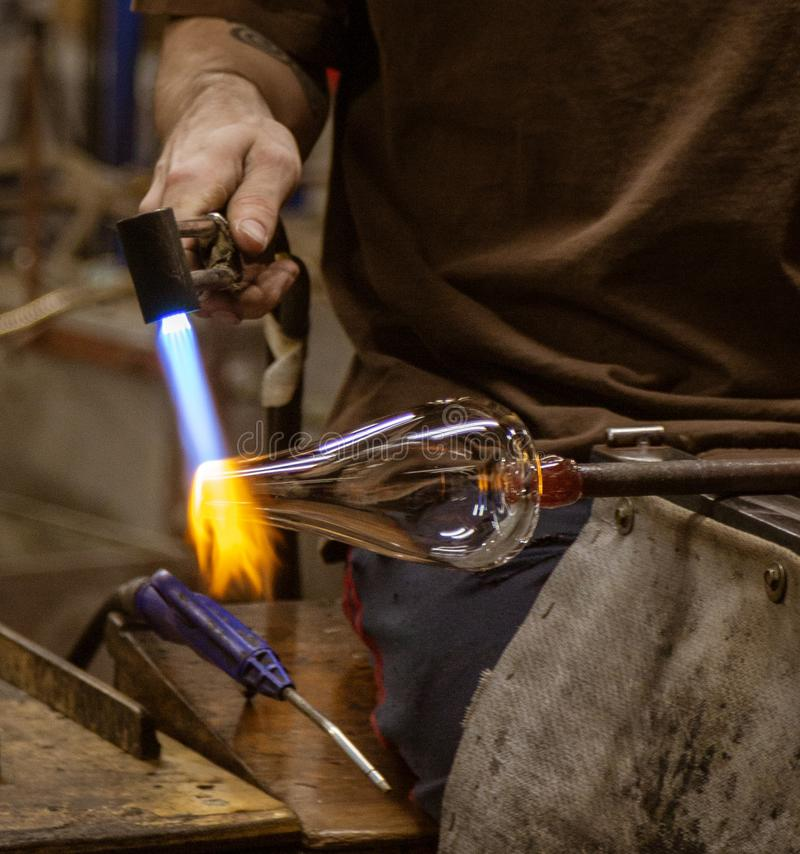A glass blowing artist forms a blob of glass into a vessel using. A gas torch in Vermont stock photography