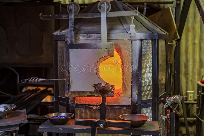 Glass blowing furnace and table with various glass blowing tools at a glass maker& x27;s workshop set up for the process stock photography