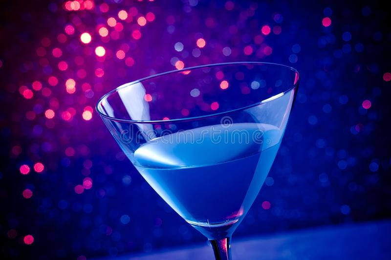 Glass blue cocktail on blue and violet tint light background. Glass blue cocktail on blue and violet tint light bokeh background on table stock image