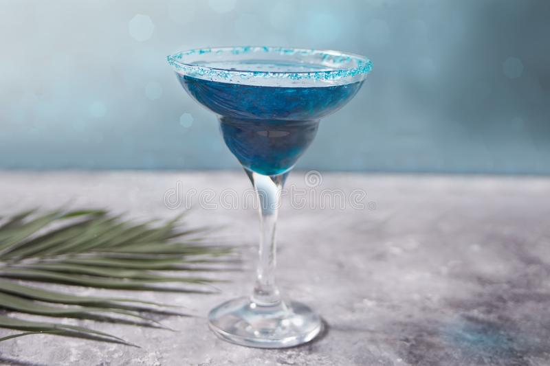 Glass of blue cocktail with the palm leaf on the concrete background. Hawaiian cocktai, lagoon cocktail, curacao. Glass of blue cocktail. Hawaiian cocktai royalty free stock photo