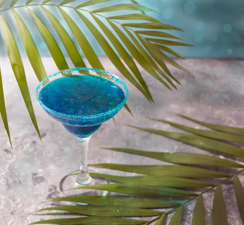 Glass of blue cocktail under the palm leaf. Hawaiian cocktai, lagoon cocktail, curacao. Glass of blue cocktail. Hawaiian cocktai, lagoon cocktail, curacao royalty free stock photography