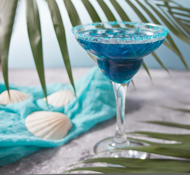 Glass of blue cocktail under the palm leaf. Hawaiian cocktai, lagoon cocktail, curacao. Glass of blue cocktail. Hawaiian cocktai, lagoon cocktail, curacao stock images