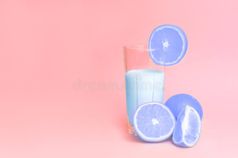 A glass with blue orange juice with the cut oranges royalty free stock photo
