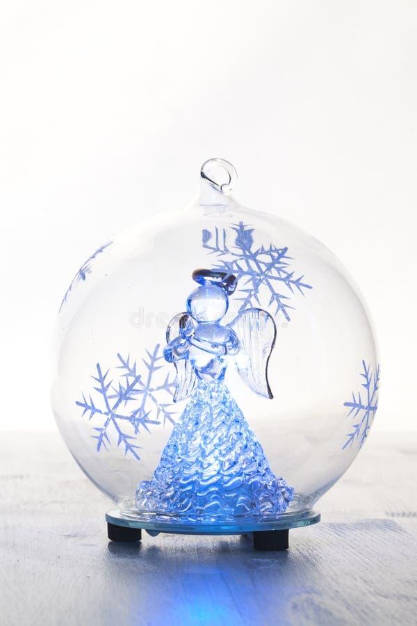 Glass boll för jul med ängel inom arkivfoto