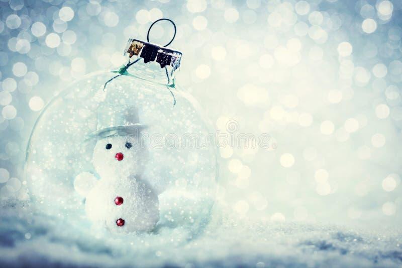 Glass boll för jul med snögubben inom Snöa och blänka royaltyfri bild