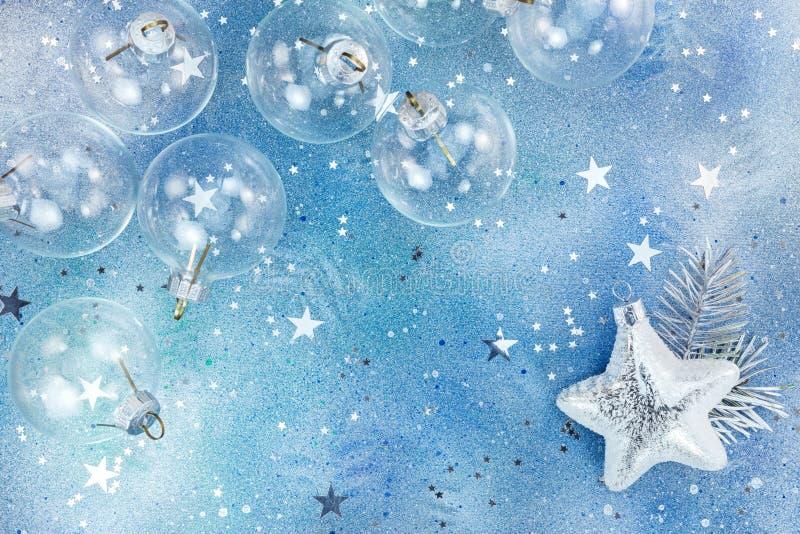 Glass bollar för jul och skinande silverstjärna på blå bakgrund w royaltyfri fotografi