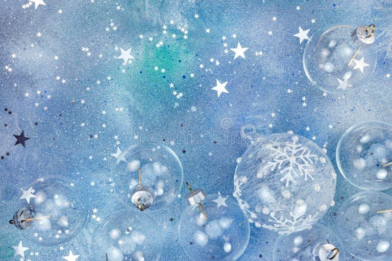 Glass bollar för jul och stjärnakonfettier på blå bakgrund royaltyfri foto