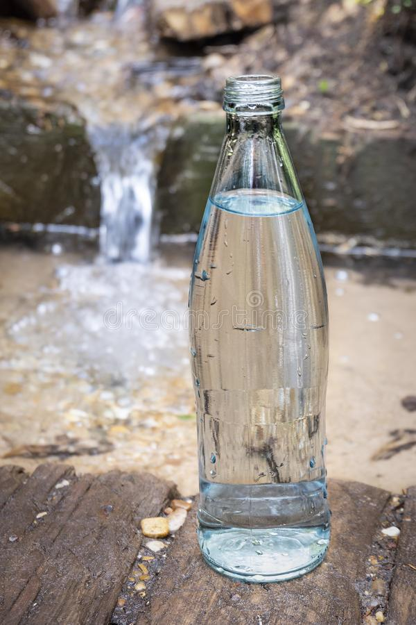 Glass bottle on the background of pure spring water. Clean natural water.  royalty free stock images