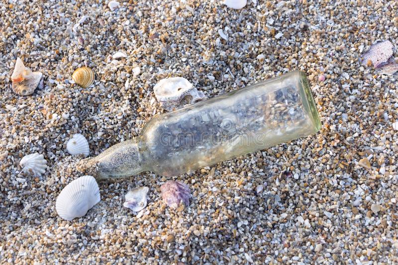A glass bottle on the beach near the sea. It`s garbage pollution stock photography