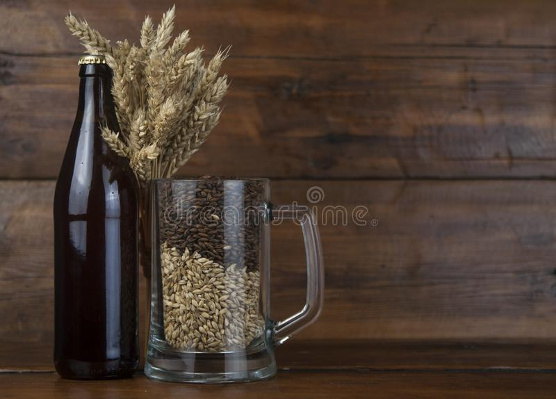 Glass and bottle of beer, ears of barley on wooden background. A stock photos