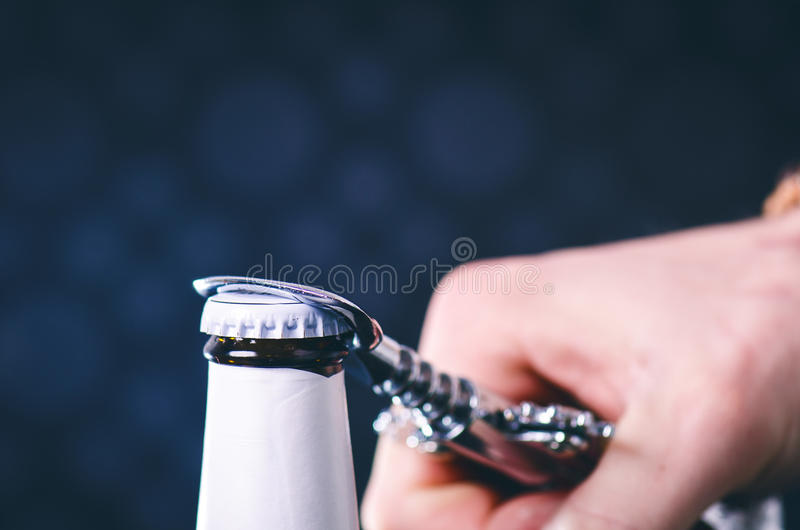 Glass bottle of beer and opener on a dark background. Hand opening a bottle. Alcohol and drinks concept. stock photography