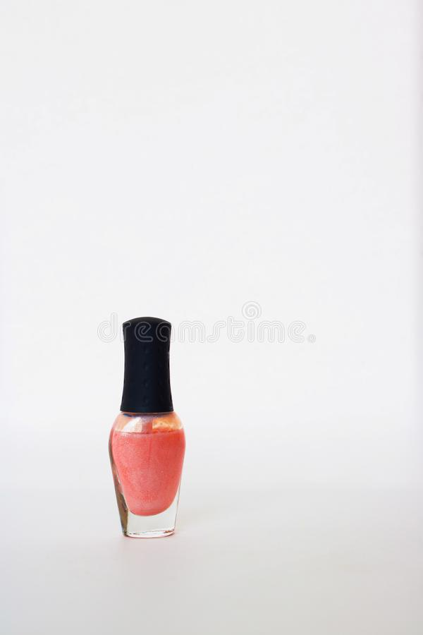 Glass bottle with black cap with pearl coral nail polish. Isolated object on white background. Nail polish. Beauty. manicure. Glass bottle with black cap with stock images