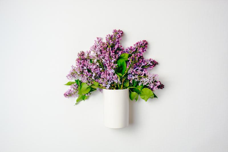 Glass bottle with blooming lilac flowers over white background. Creative flat lay composition, top view, overhead. Spring flowers stock image