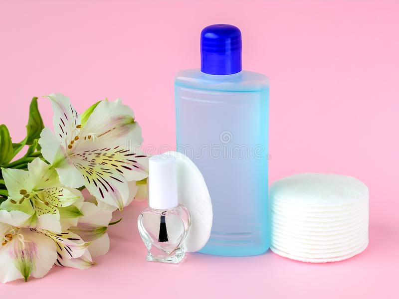 Glass bottle with colorless nail polish, plastic bottle with nail varnish remover, cotton pads and white flowers on a pastel pink royalty free stock photo