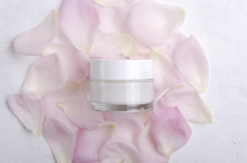 Top view of closed glass jar full of moisturizing cream on the pink rose petals stock image