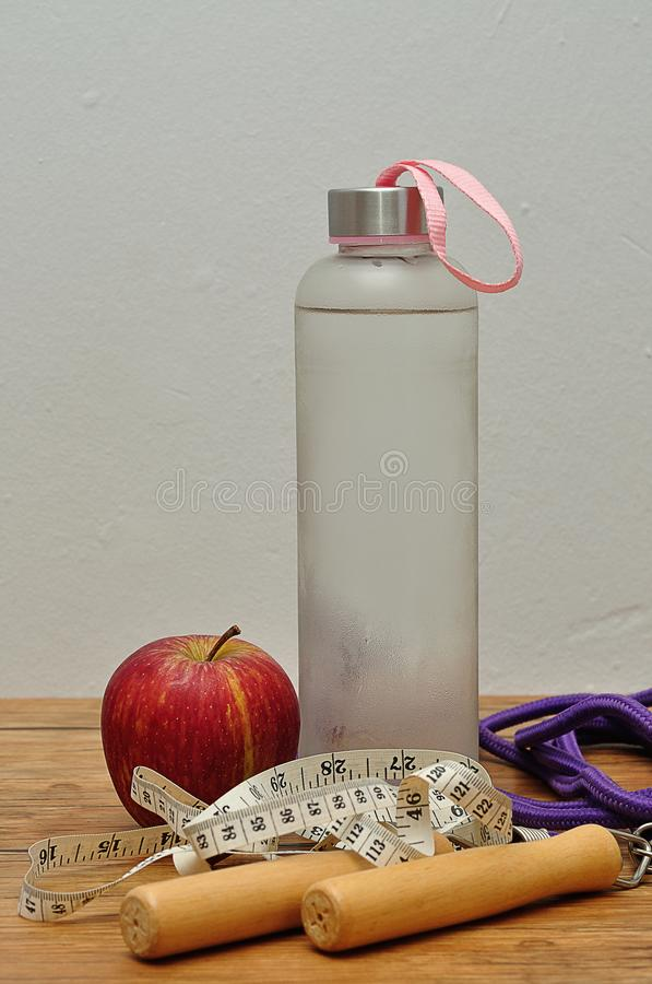 A glass bottle filled with ice cold water, a measuring tape, an apple and a jumping rope royalty free stock images