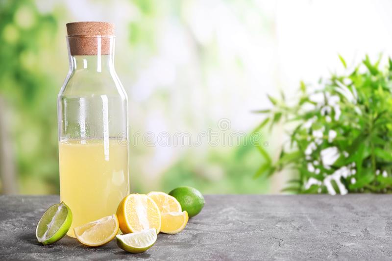 Glass bottle with fresh citrus juice and fruits. On table royalty free stock photos