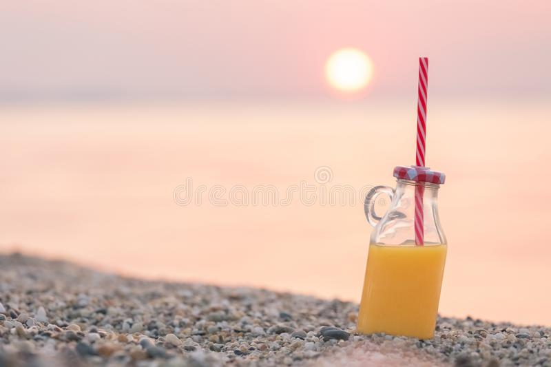 Glass bottle of fresh orange juice on beach at sunset over sea. Glass of orange juice with drinking straw on beach. Sunset and ocean in the background. Healthy royalty free stock images