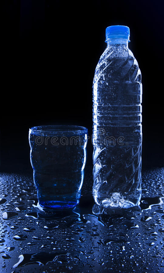 Glass and bottle on freshness drinking water on wet floor with c royalty free stock images