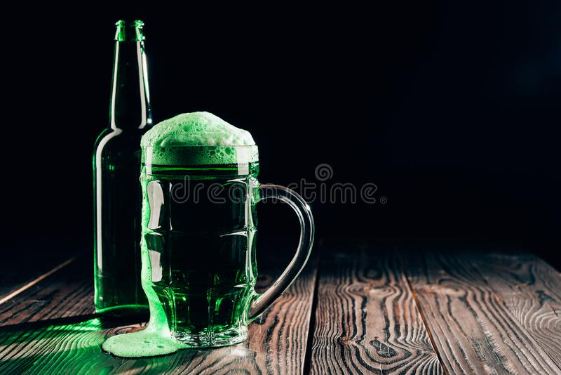glass and bottle of green beer on wooden table, st patricks day concept stock photography
