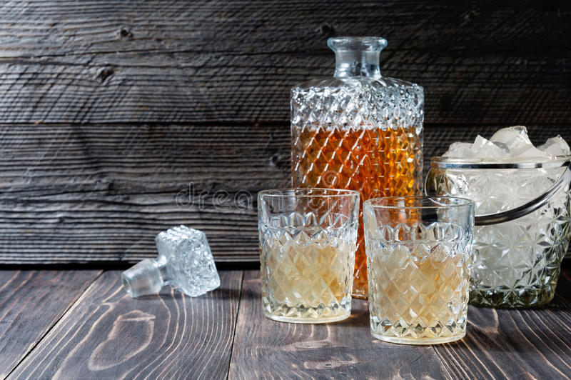 Glass and bottle of hard liquor like scotch, bourbon, whiskey or brandy on wooden background with copyspace stock image