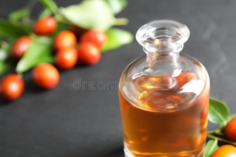 Glass bottle with jojoba oil and seeds on stone table, closeup. Space for text. Glass bottle with jojoba oil and seeds on grey stone table, closeup. Space for stock photography