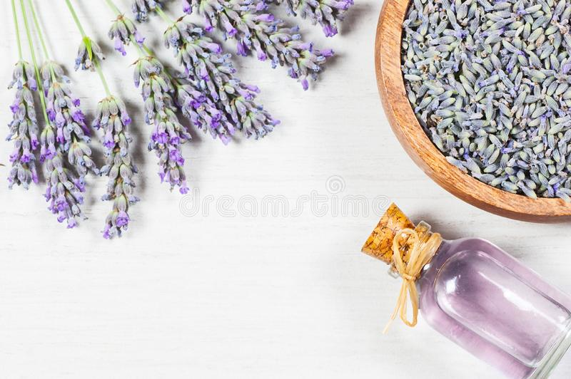Glass bottle of Lavender essential oil with fresh lavender flowers and dried lavender seeds on white rustic table royalty free stock images