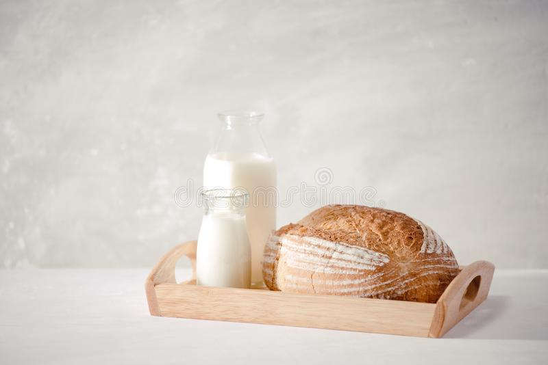 Glass bottle of milk with bread on wooden tray for food and healthy concept stock photo