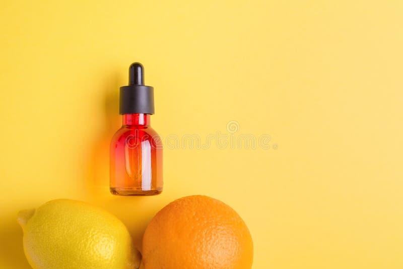 Glass bottle, orange, lemon on a yellow background. Organic bio cosmetics with vitamin C. Concept Minimalism Flat lay. Glass bottle and orange on a yellow stock photo