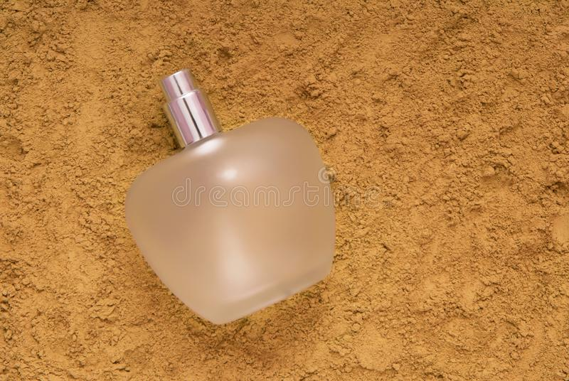 Glass bottle of perfume is on the sand stock image
