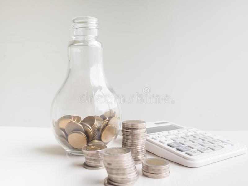 Glass bottle Piggy bank and calculator  with coins pile, Saving money for future plan and retirement fund concept.  royalty free stock images