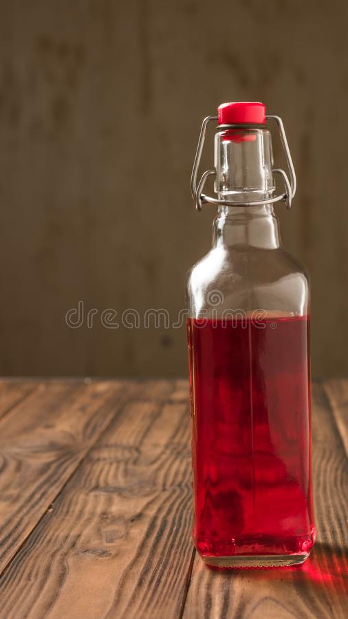 Glass bottle with plum alcohol on a wooden table. Homemade alcoholic drink made from berries plum royalty free stock photos