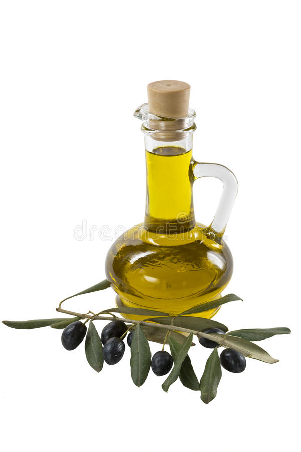Glass bottle of premium olive oil and some ripe olives with a branch stock photo