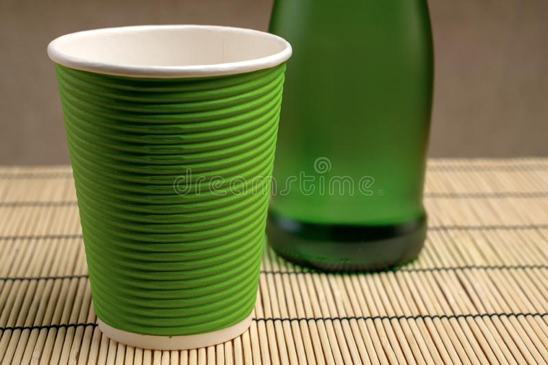 Glass bottle with pure mineral drinking water and paper cup. Close-up. Glass bottle with pure mineral drinking water and paper cup. Clouse-up stock photos