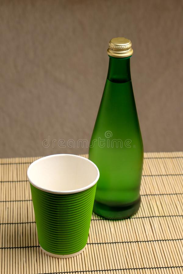 Glass bottle with pure mineral drinking water and paper cup. Ecological dishes. Glass bottle with pure mineral drinking water and paper cup stock photos