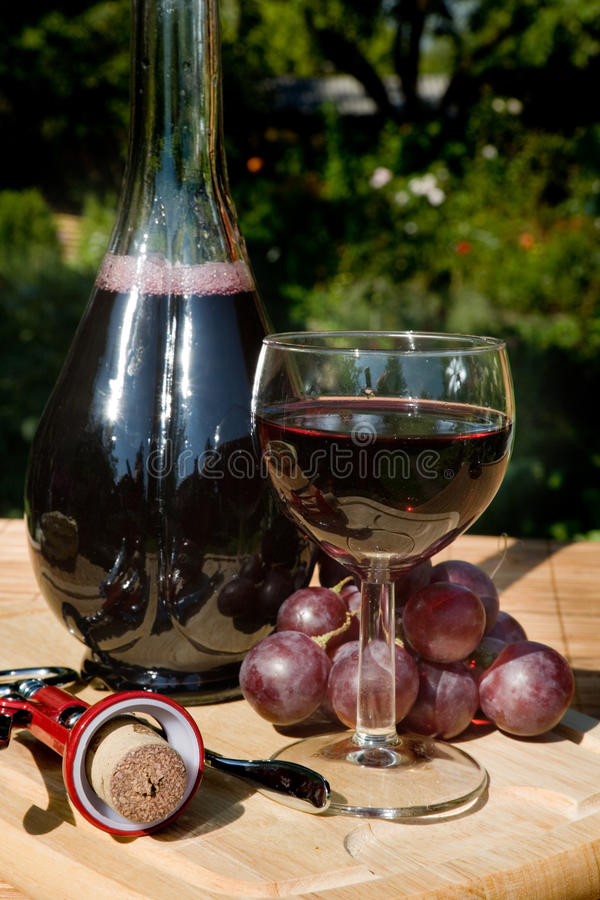 Glass and bottle of red wine. With corkscrew royalty free stock images