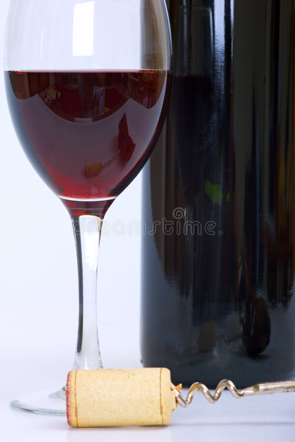 Glass and bottle of red wine with cork and corkscrew royalty free stock image