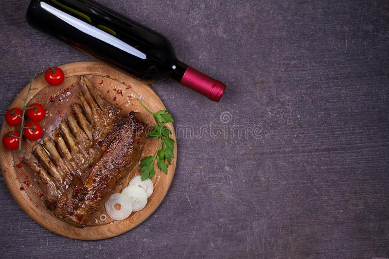 Glass and bottle of red wine with lamb chops. Wine and meat. Wine and food conception. royalty free stock image