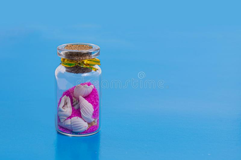 Glass bottle with shells and pink sand on a blue background. The concept of vacation and travel to exotic places, souvenir royalty free stock photo