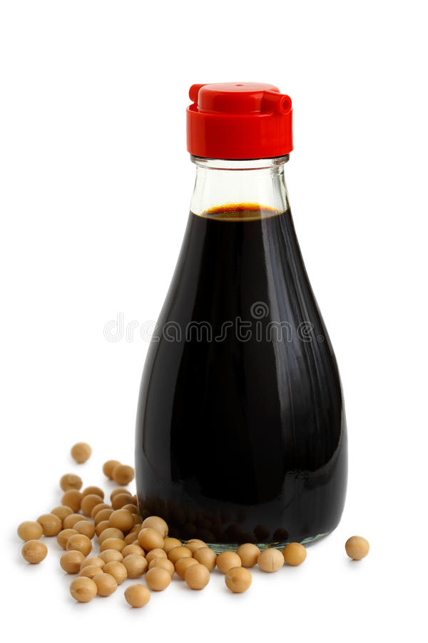 Glass bottle of soya sauce with red plastic lid isolated on whit. E. Spilled soya beans stock photo