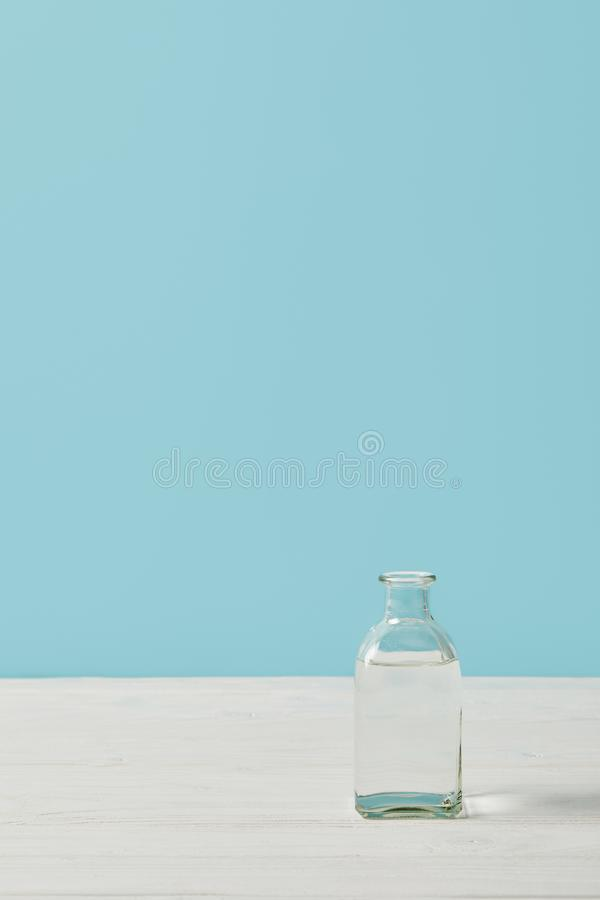 Glass bottle of water on white tabletop isolated on blue royalty free stock image