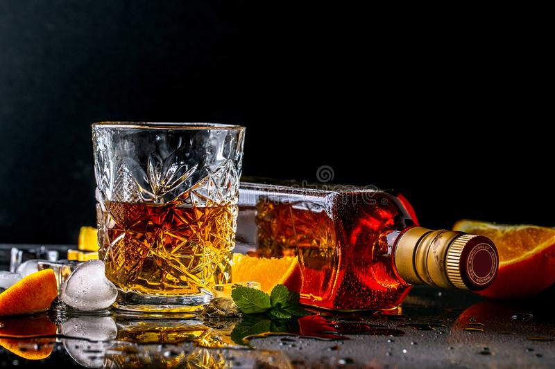 Glass and bottle of whiskey drink with ice cube on black bar background. copy space. concept luxury drink royalty free stock photos