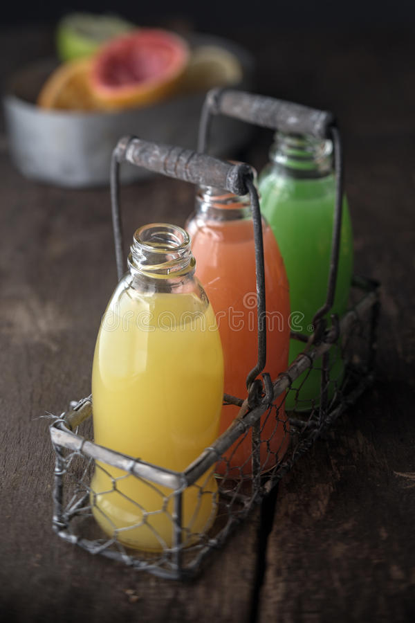 Glass bottles of assorted fresh fruit juice royalty free stock photography