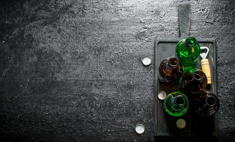 Glass bottles of beer on a black cutting Board royalty free stock photo