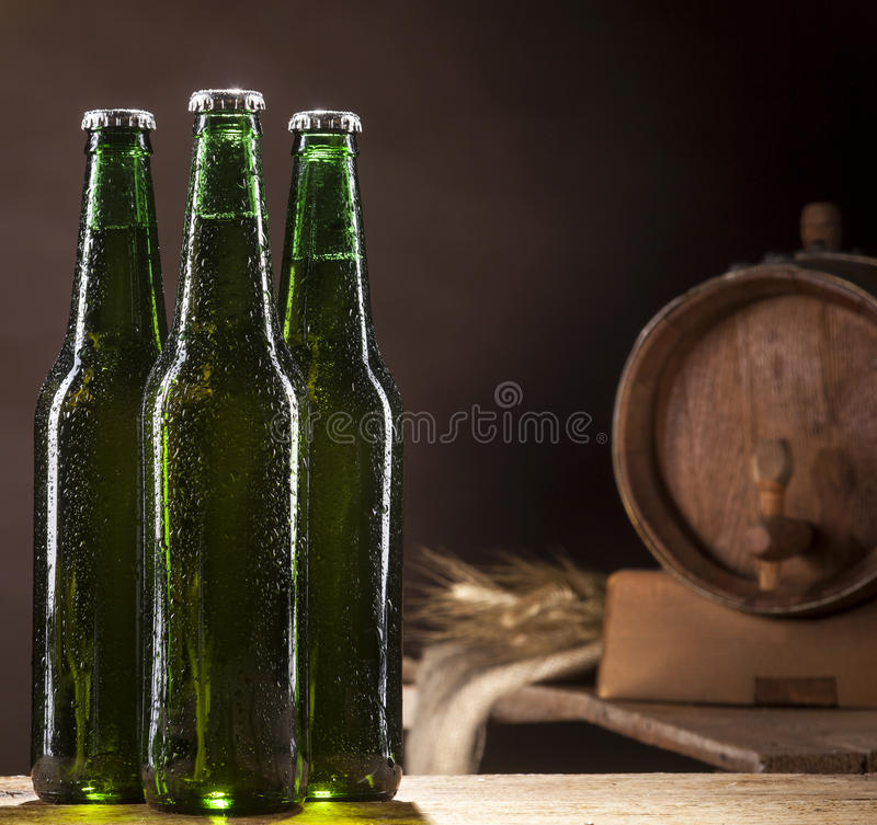 Glass bottles of beer and wooden barrel on brown background royalty free stock image