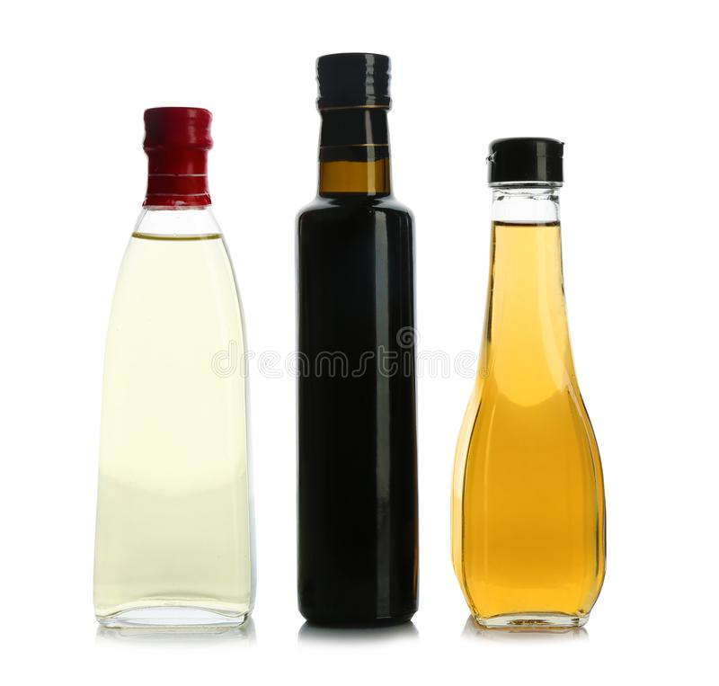 Glass bottles with different kinds of vinegar. On white background stock photography