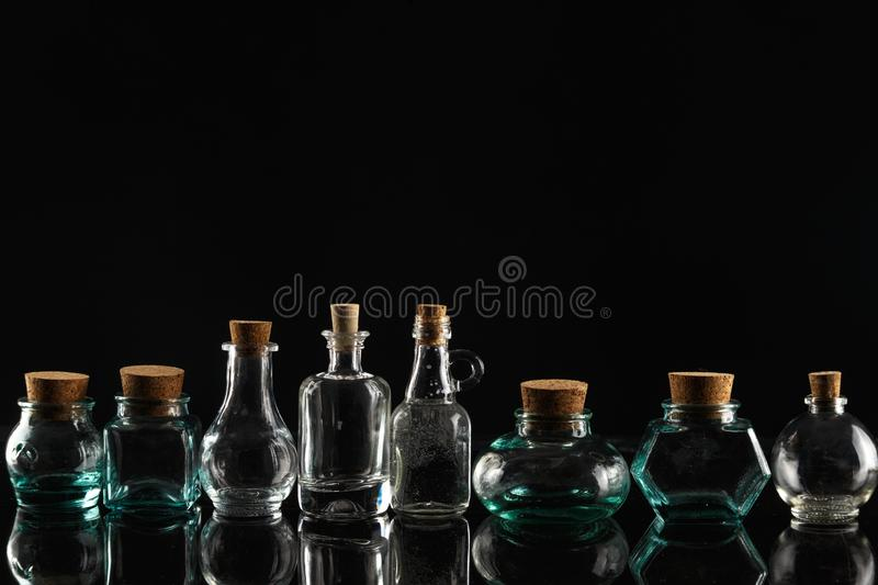 Glass bottles of different shapes and sizes on a black background royalty free stock photo